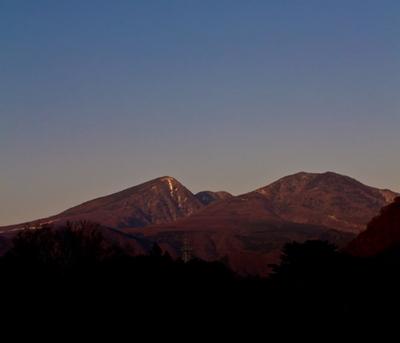 夕暮れ時の雪が残る山